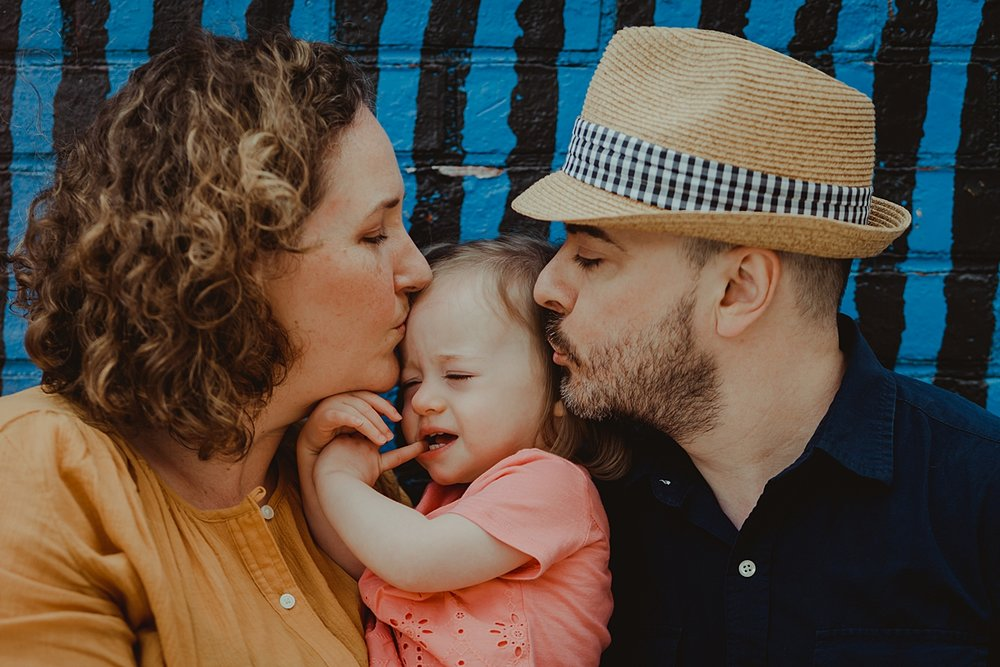 photo of dad and mom kissing youngest daughter in front of bright and colorful graffiti wall in dumbo brooklyn. photo by nyc family and newborn photographer krystil mcdowall