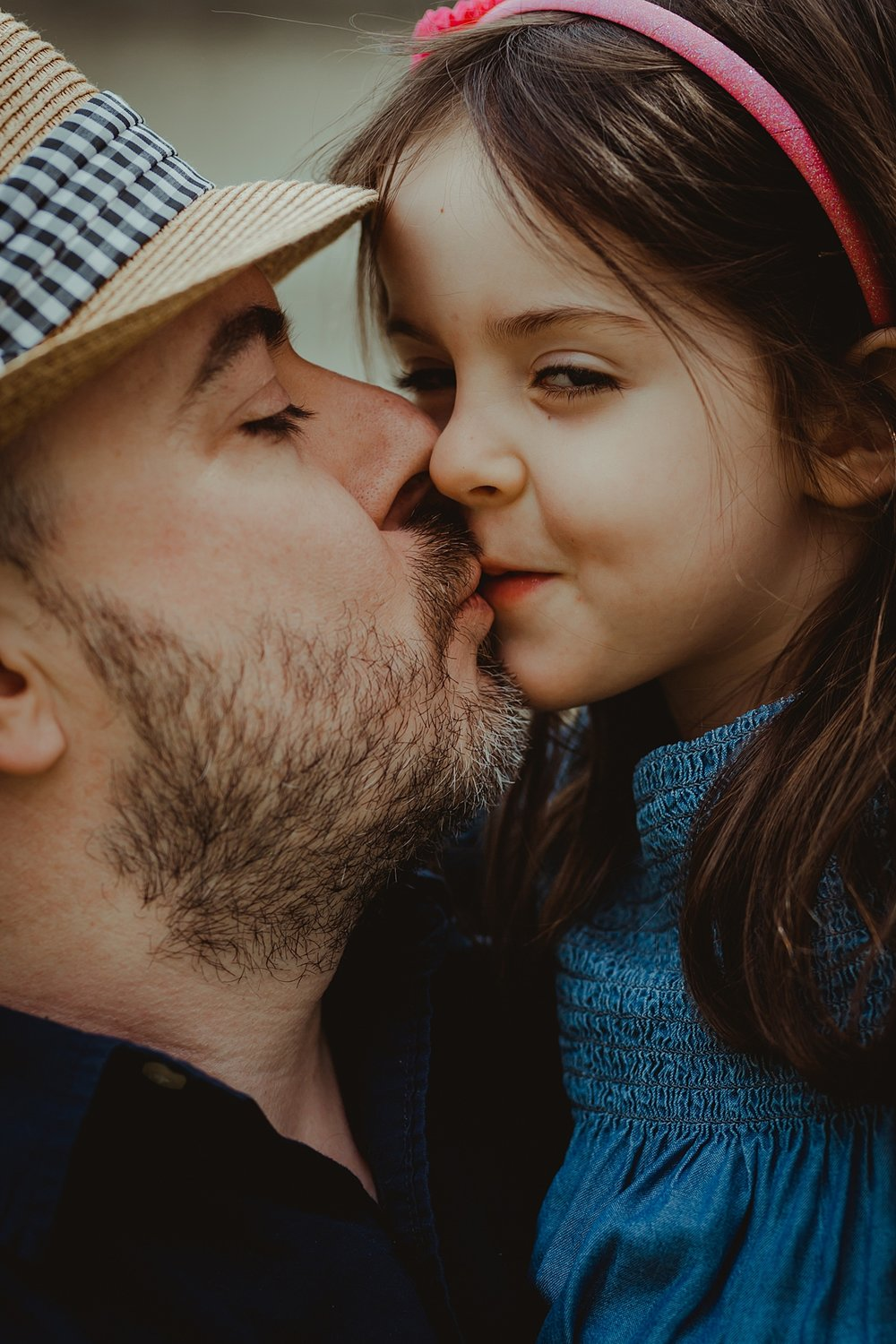 portrait of dad kissing daughter on the lips and daughter looking at camera with cheeky grin. photo by nyc family and newborn photographer krystil mcdowall