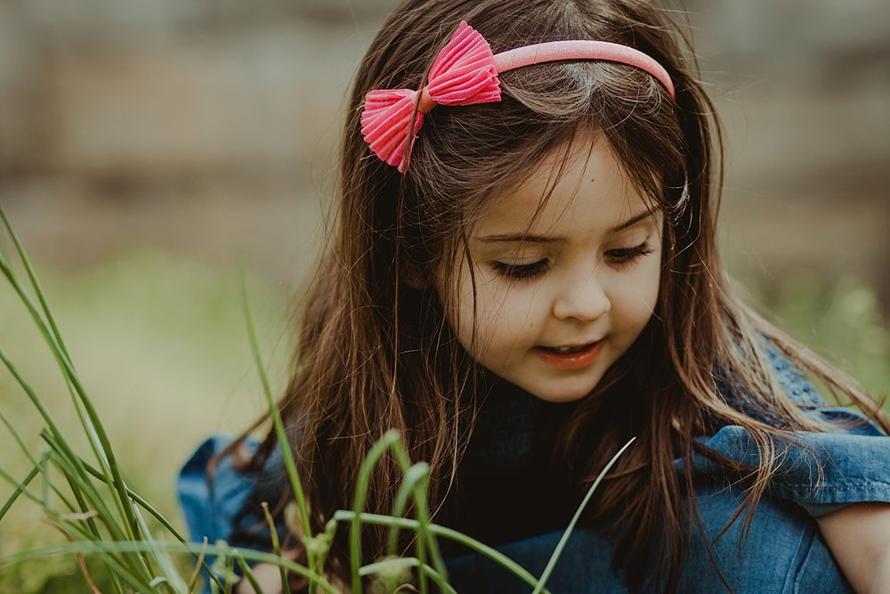 young girl exploring green grass and yellow dandelions during family photo session in new york city. photo by nyc family and newborn photographer krystil mcdowall