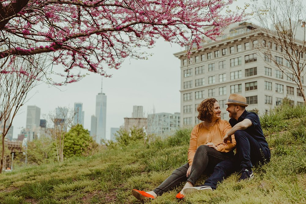 portrait of mom and dad sitting on green hill with cherry blossoms overhanging and manhattan buildings in the background. photo by nyc family and newborn photographer krystil mcdowall