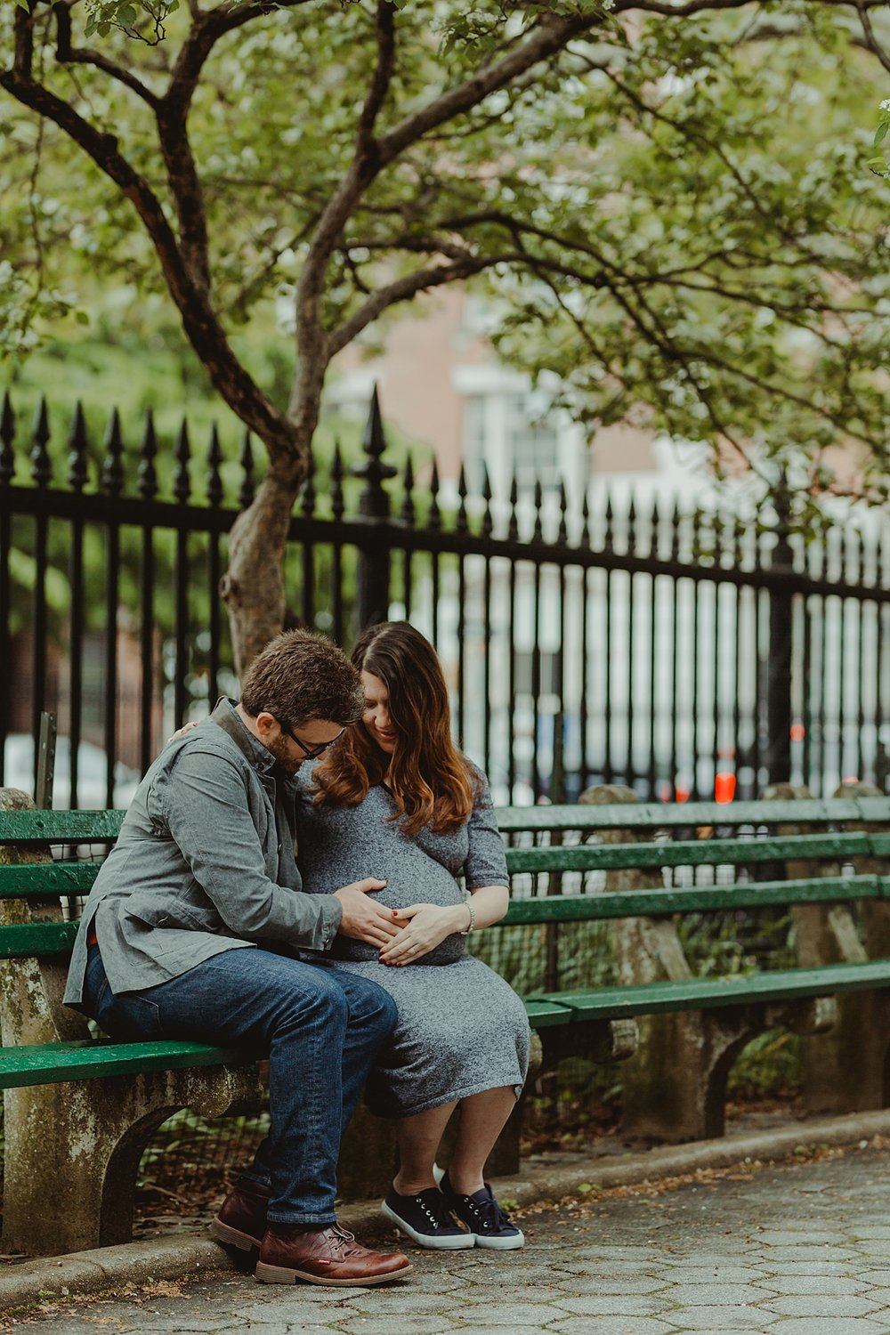 photo of expecting mom and dad sitting on park bench with dad touching mom's belly during maternity photo session. photo by nyc family and newborn photographer krystil mcdowall