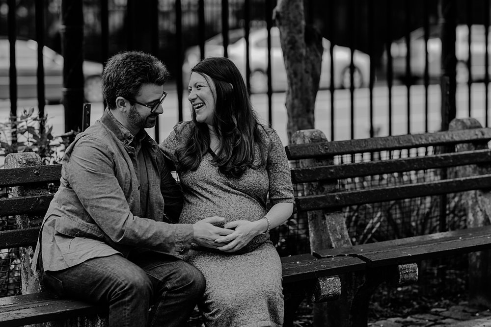 black and white photo of expecting mom and dad sitting on park bench in stuyvesant square with dad touching mom's belly and mom laughing during maternity photo session. photo by nyc family and newborn photographer krystil mcdowall