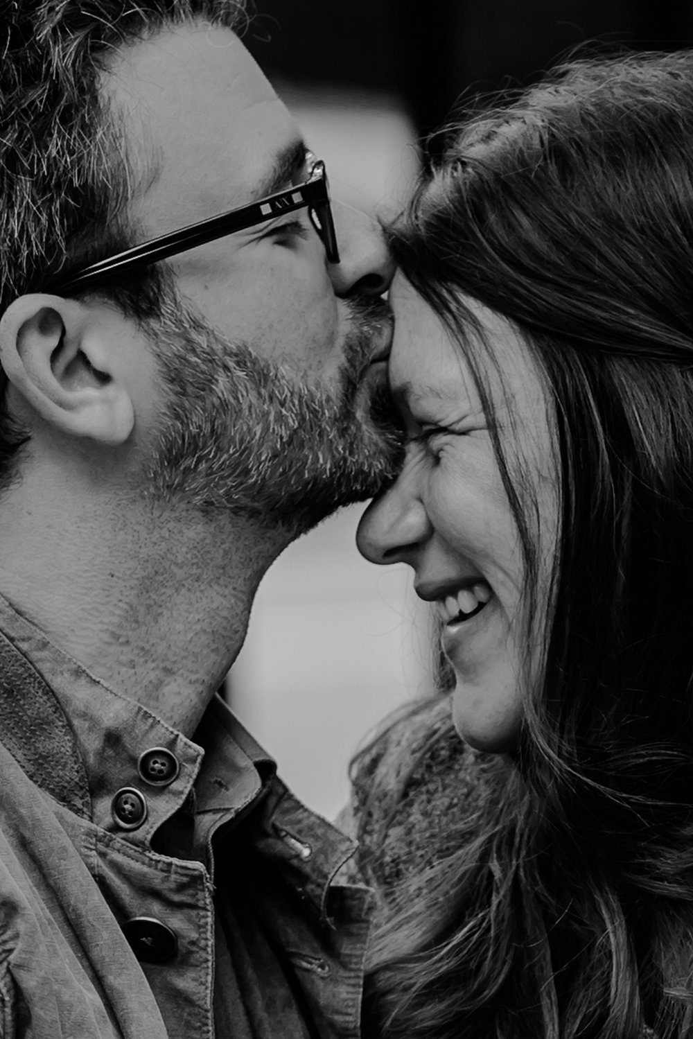black and white close up portrait of expecting dad kissing mom's forehead while mom's laughs during maternity photo session in stuyvesant square nyc. photo by nyc family and newborn photographer krystil mcdowall