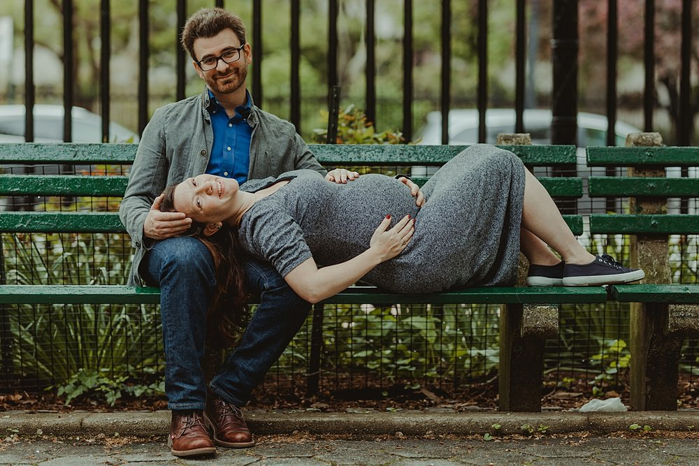 portrait of expecting mom laying down on park bench straddled across dad's lap with both parents looking at the camera during maternity photo session in stuyvesant square nyc. photo by nyc family and newborn photographer krystil mcdowall
