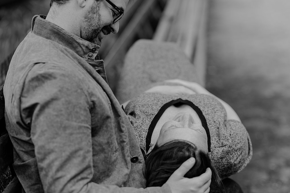 black and white photo of expecting mom laying down on park bench across dad's lap during maternity photo session in nyc. photo by nyc family and newborn photographer krystil mcdowall