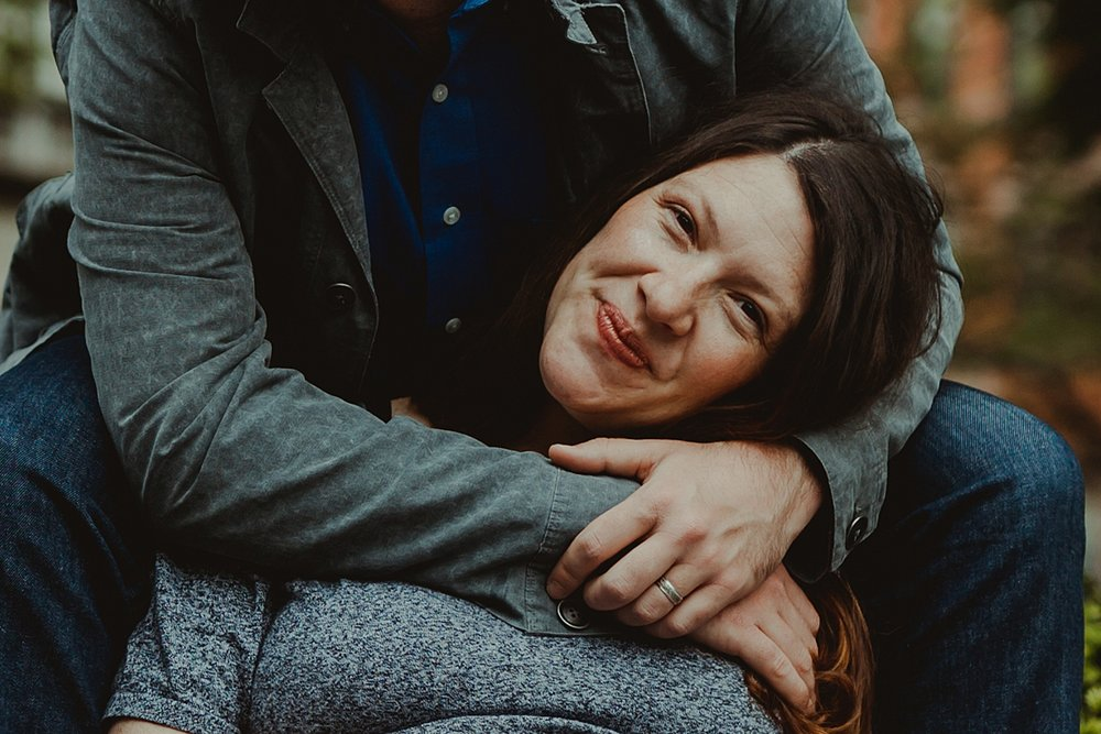 portrait of expecting mom smiling for the camera while her husband's arms are wrapped around her for a hug. photo by nyc family and newborn photographer krystil mcdowall