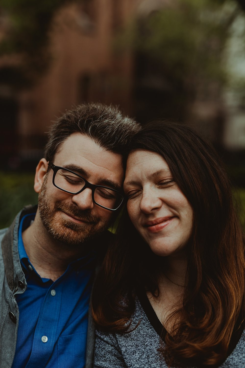 portrait of expecting husband and wife with their eyes closed during outdoor maternity photo session in new york city. photo by nyc family and newborn photographer krystil mcdowall