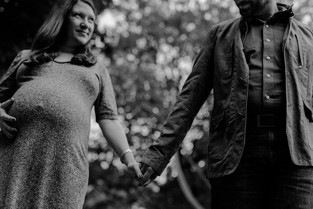 image of expecting husband and wife holding hands walking in stuyvesant square park during outdoor maternity photo session in new york city. photo by nyc family and newborn photographer krystil mcdowall
