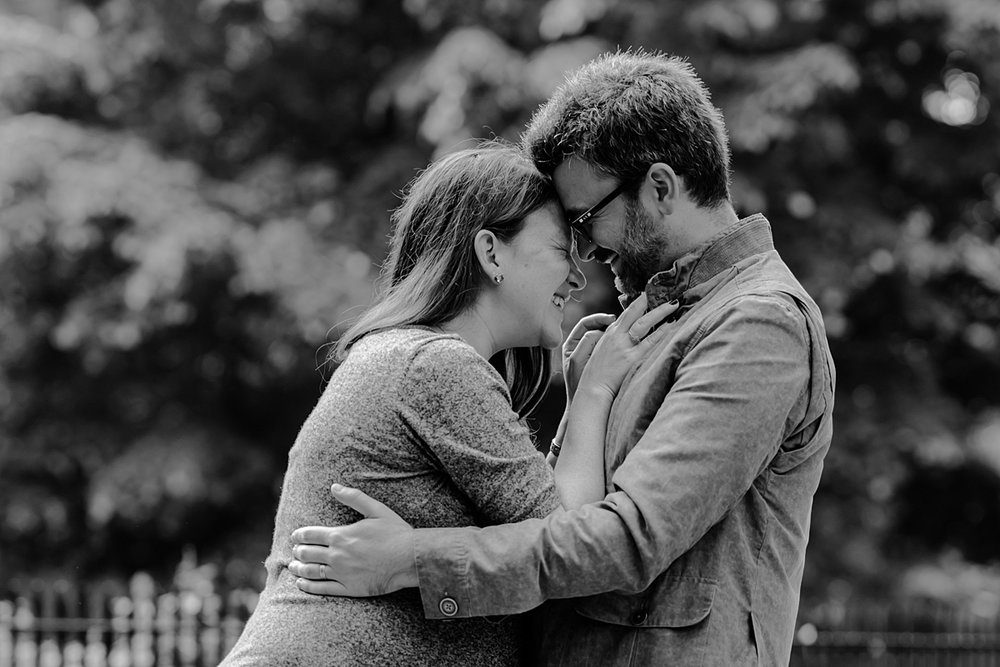 black and white candid photo of expecting husband and wife hugging and laughing in the park during their nyc maternity photo session. photo by nyc family and newborn photographer krystil mcdowall