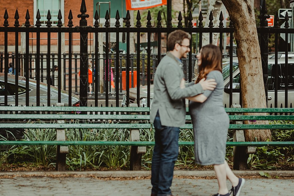 blurred image of pregnant husband and wife in the park during their nyc maternity photo session. photo by nyc family and newborn photographer krystil mcdowall