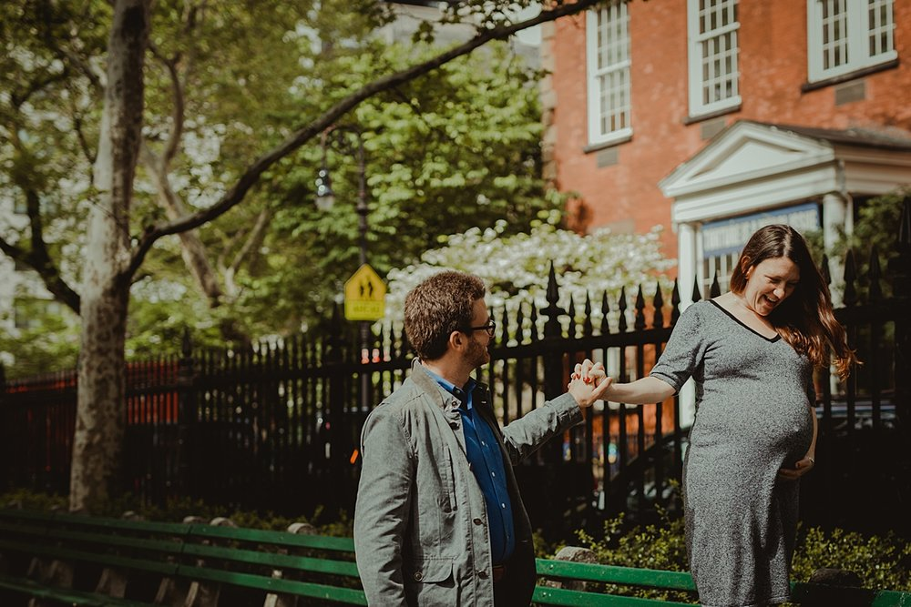 image of pregnant husband and wife in the park with pregnant mom walking along park bench while her husband holds her hand during nyc outdoor maternity photo session. photo by nyc family and newborn photographer krystil mcdowall