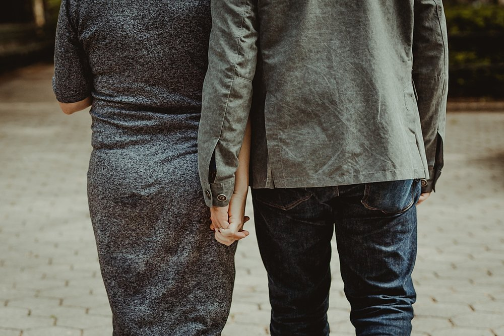 close up image of pregnant husband and wife holding hands and walking away from the camera during outdoor maternity photo session. photo by nyc family and newborn photographer krystil mcdowall