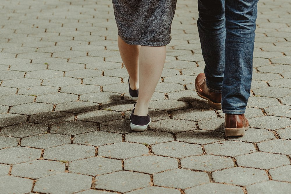 close up image of shoes of pregnant husband and wife walking away from the camera during outdoor maternity photo session. photo by nyc family and newborn photographer krystil mcdowall