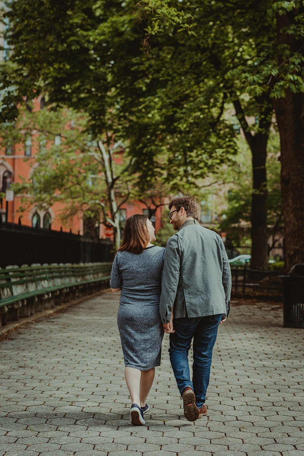 image of pregnant husband and wife holding hands and walking away from the camera during outdoor maternity photo session in stuyvesant square park. photo by nyc family and newborn photographer krystil mcdowall