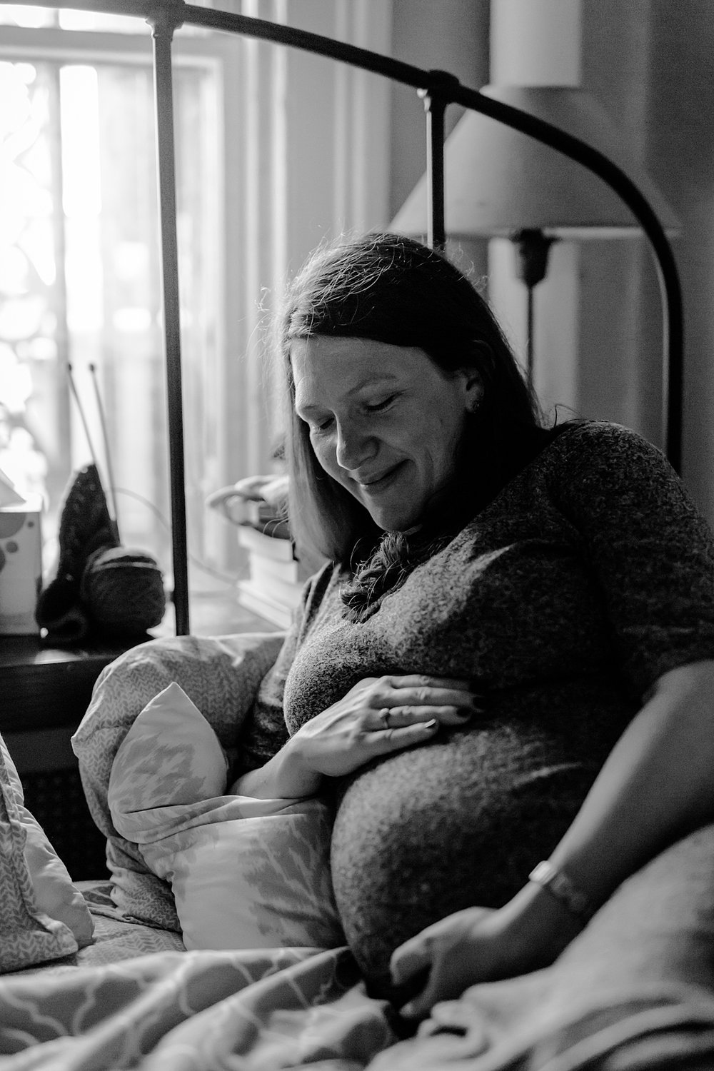 black and white maternity portrait of expecting mother sitting in her bedroom and holding her big pregnant belly. photo by nyc family and newborn photographer krystil mcdowall
