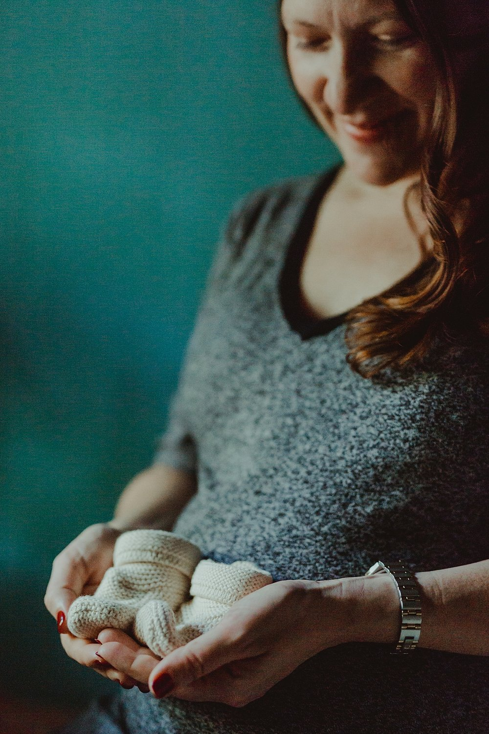 close up portrait of expecting mother holding white knitted baby shoes in front of her pregnant belly and looking down adoringly at the shoes during maternity photo session. photo by nyc family and newborn photographer krystil mcdowall