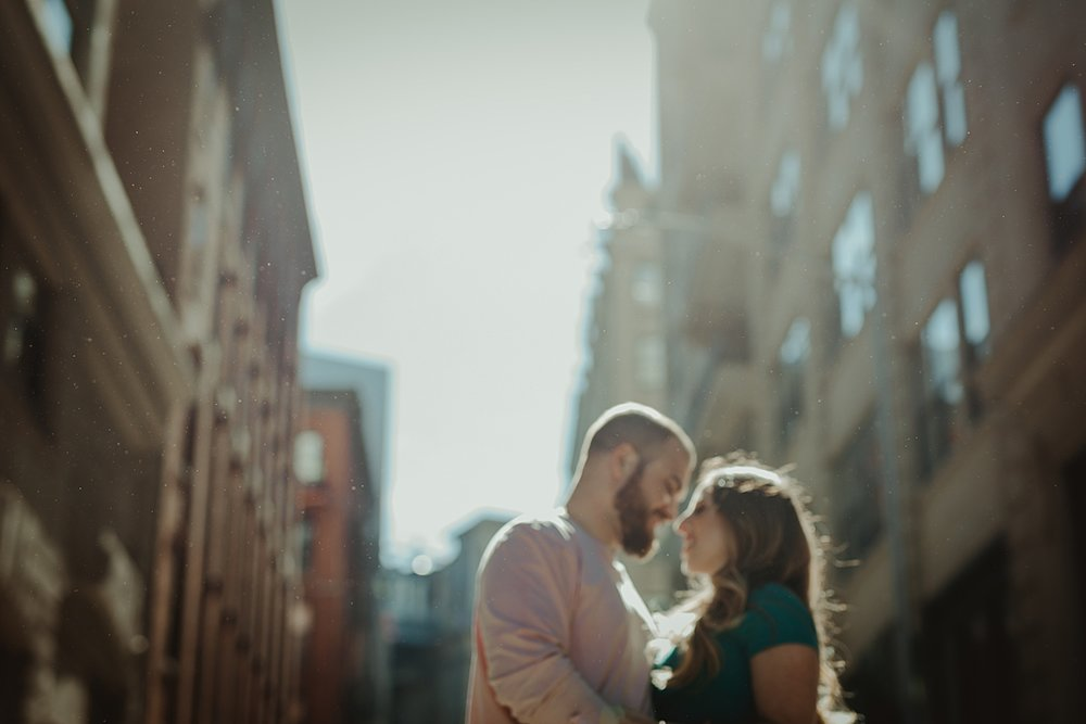 blurred color photo of pregnant couple standing with sun behind them on a cobble stoned street during their maternity photo shoot in brooklyn. image by nyc family and newborn photographer krystil mcdowall