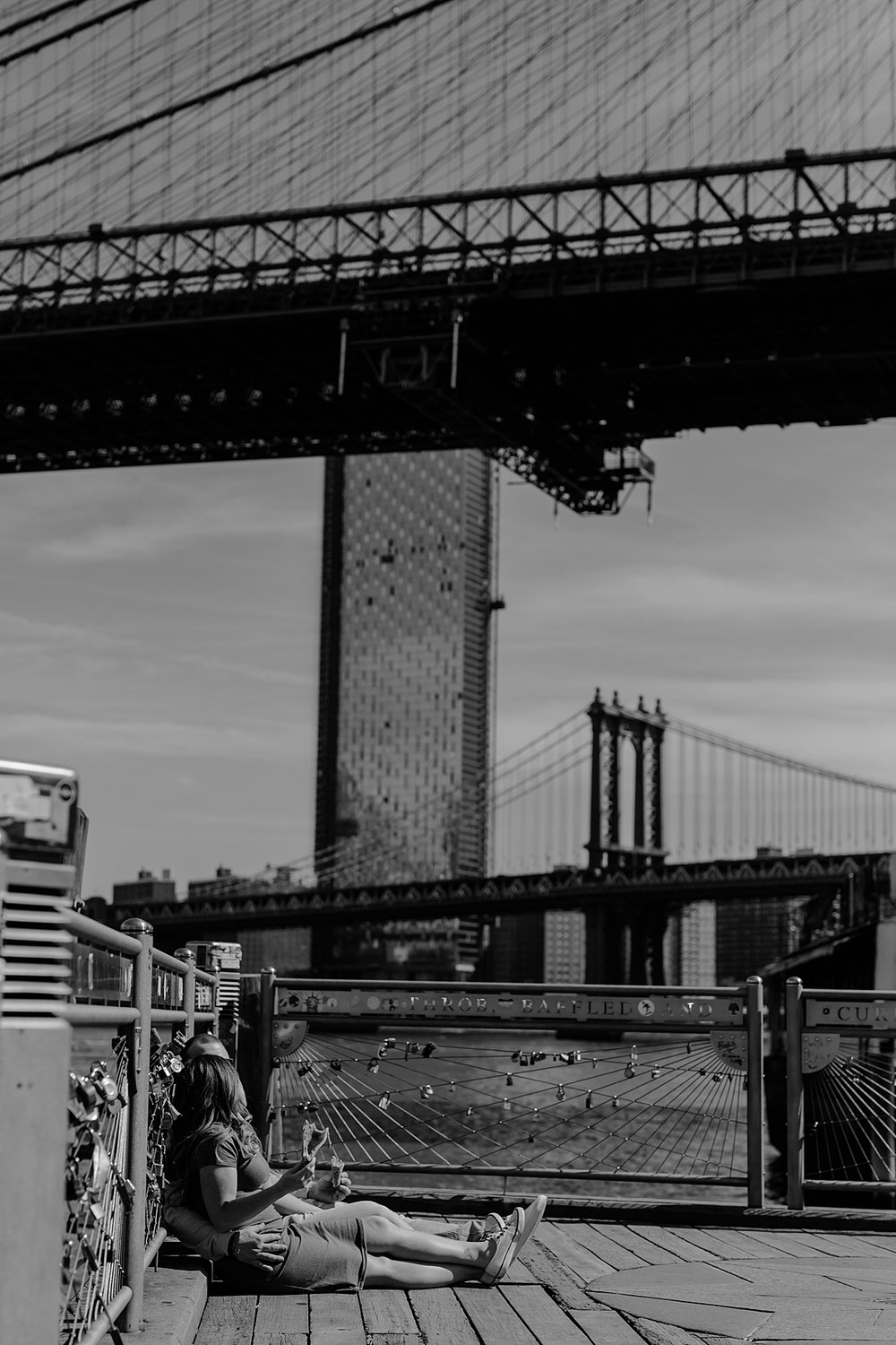 black and white photo of pregnant couple laughing and eating pizza while sitting on the pier at brooklyn bridge park during maternity photo shoot. image by krystil mcdowall photography
