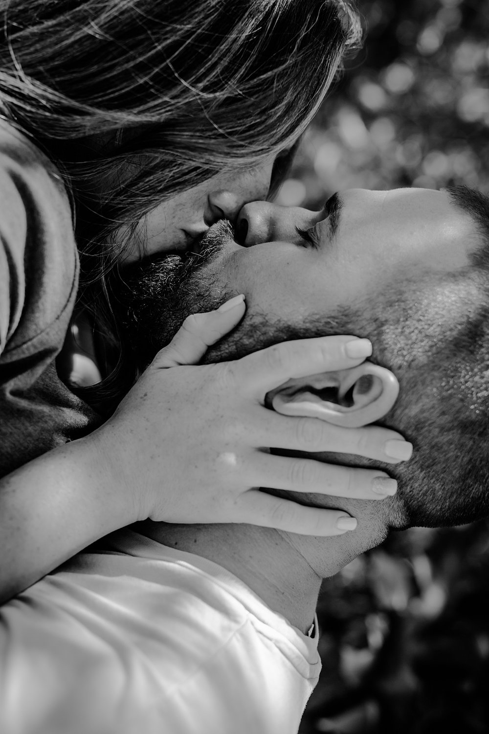 close up black and white portrait of husband holding pregnant wife in the air and kissing during maternity photo shoot in brooklyn. image by krystil mcdowall photography