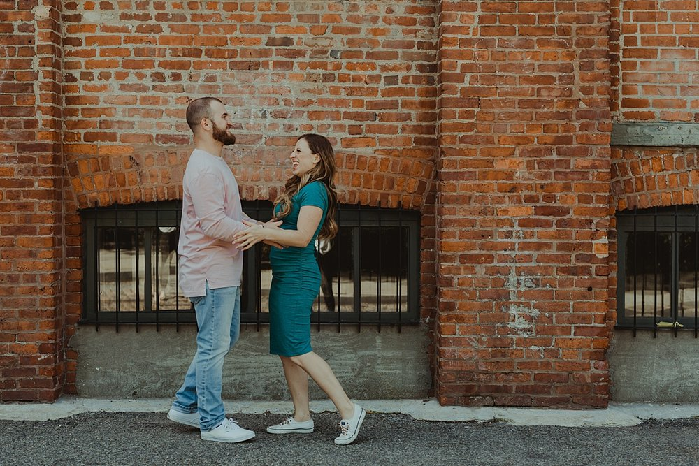 color image of husband and wife laughing in front of gritty brick wall in dumbo brooklyn during maternity photo shoot. image by krystil mcdowall photography