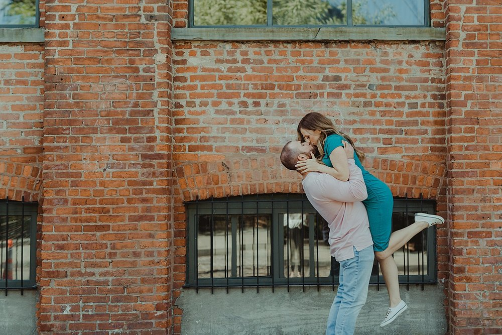color image of husband and wife kissing in front of gritty brick wall in dumbo brooklyn during maternity photo shoot. image by krystil mcdowall photography