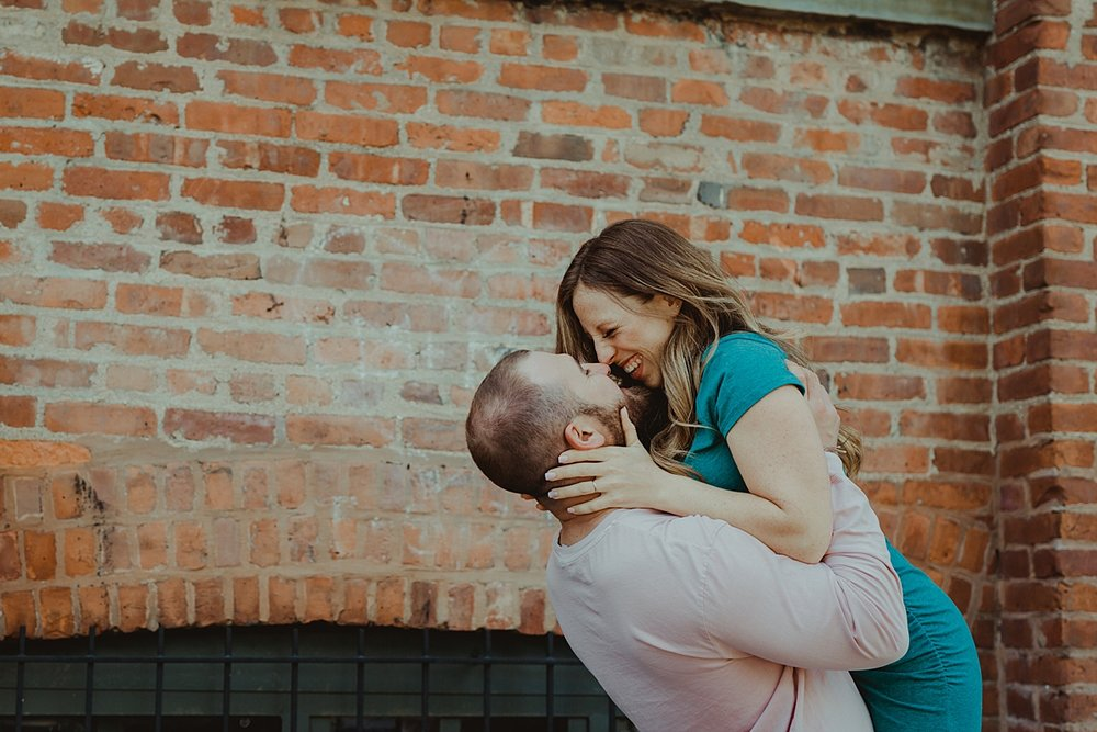 color image of husband holding pregnant wife in the air while she's laughing in front of gritty brick wall in dumbo brooklyn during maternity photo shoot. image by krystil mcdowall photography