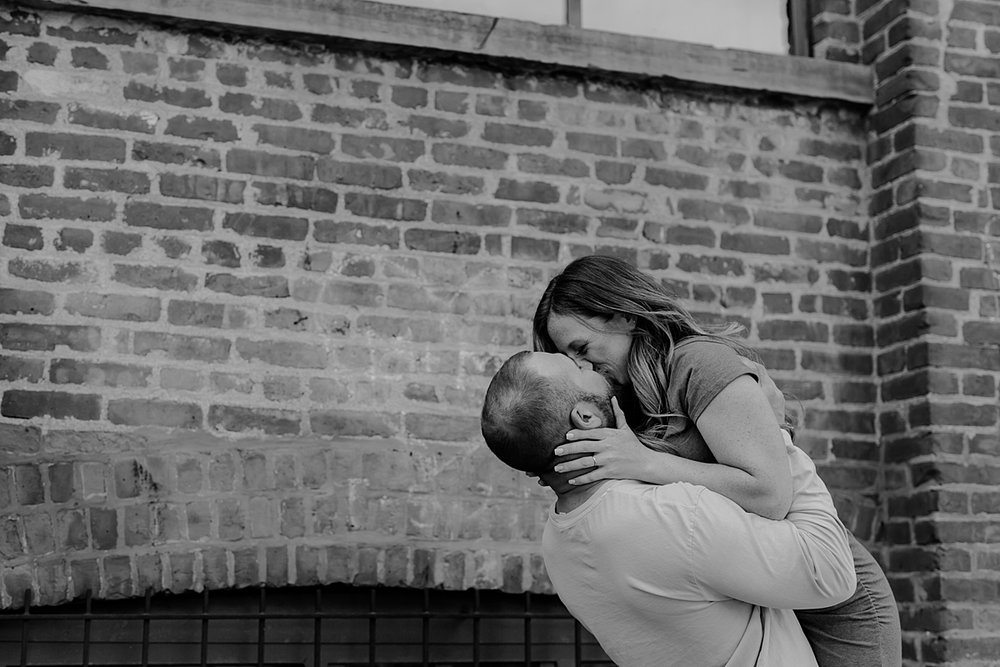 husband and wife laughing and kissing in front of gritty brick wall in dumbo brooklyn during maternity photo shoot. image by krystil mcdowall photography