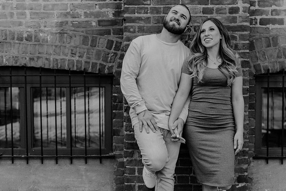 black and white image of husband and wife looking out at the manhattan skyline while leaning again gritty brick wall in dumbo brooklyn during maternity photo shoot. image by krystil mcdowall photography