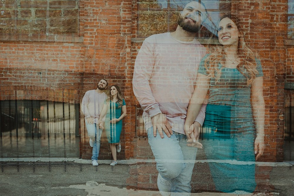 double exposure photo of husband and wife looking out at the manhattan skyline while leaning again gritty brick wall in dumbo brooklyn during maternity photo shoot. image by krystil mcdowall photography