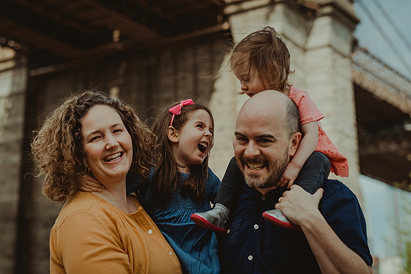 family of four candidly pose for family portraits with girls laughing at each other while sitting on mom and dad's shoulders.photo by orange county family photographer krystil mcdowall