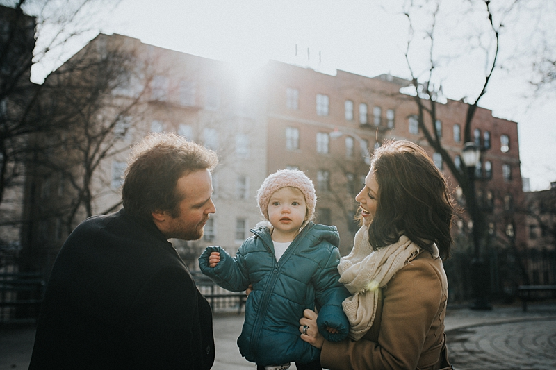 mom, dad and one year old girl sitting on park bench with burst of morning sunlight in the background.photo by orange county family photographer krystil mcdowall