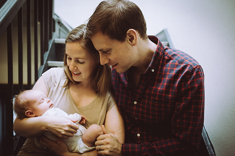 photo of mom, dad and newborn baby girl sitting in their stairwell during newborn photo session with orange county family photographer krystil mcdowall