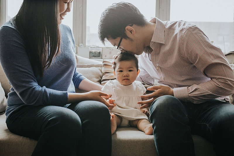 photo of mom, dad and daughter sitting on couch backlit by gorgeous window light while dad kisses daughter on the head and mom looks on happily.photo by orange county family photographer krystil mcdowall