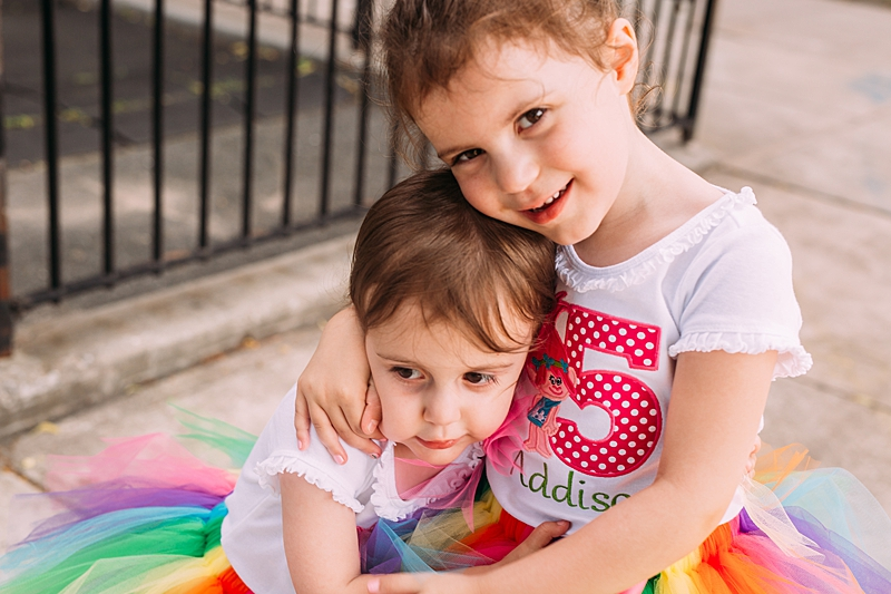 photo of two young sisters dressed in rainbow tutus before their joint birthday party. photo by orange county family photographer krystil mcdowall