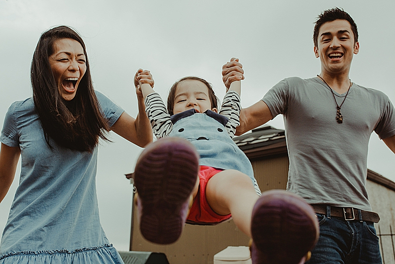 candid photo taken from below of mom and dad swinging young black haired daughter in the air while all laughing during candid family photo session with orange county family photographer krystil mcdowall