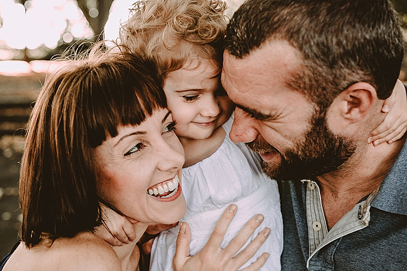 mom, dad and young daughter all squished in close together smiling and laughing during lifestyle family photo session with orange county family photographer krystil mcdowall