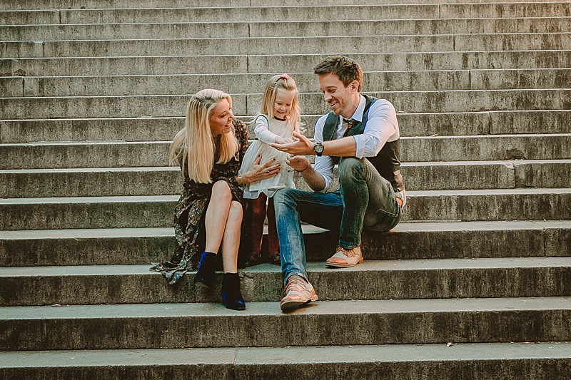 family of three dressed up beautifully and sitting on steps of local park enjoying some family time during candid family photo session with krystil mcdowall photography