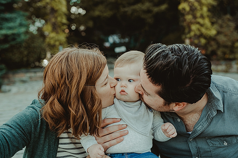 sweet mom, dad and eight month old son sit on steps at local park near big green bushes and give cute son a kiss. photo by orange county family photographer krystil mcdowall