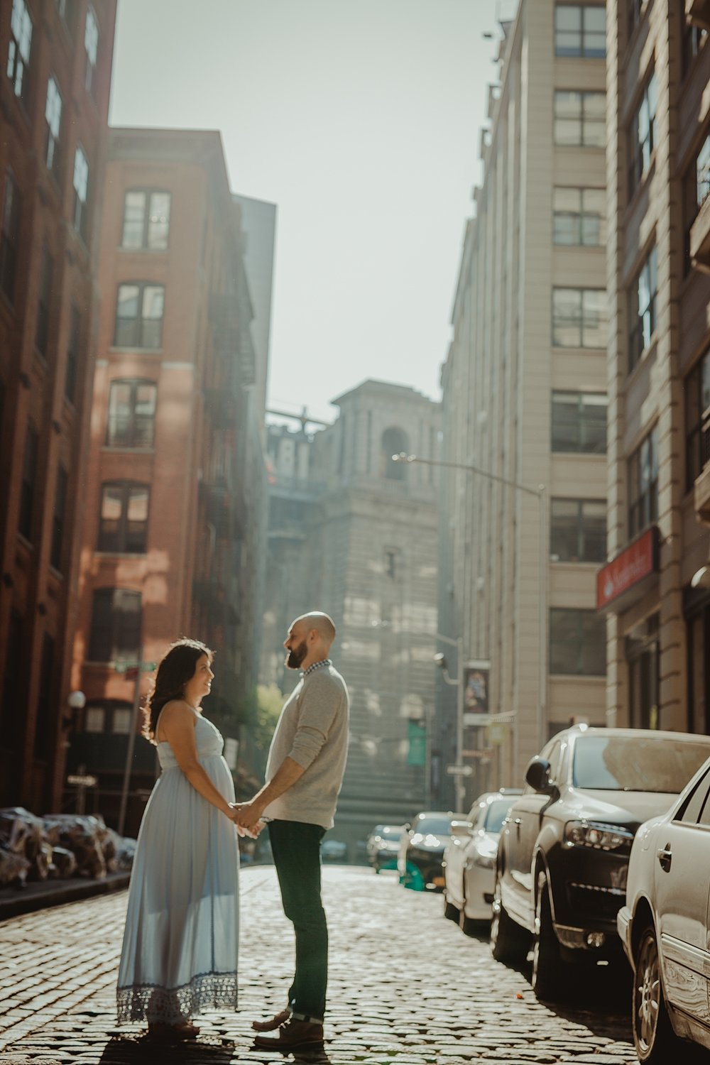photo of expecting married couple standing on cobble stoned street and holding hands during outdoor maternity photo session with orange county family photographer krystil mcdowall photography
