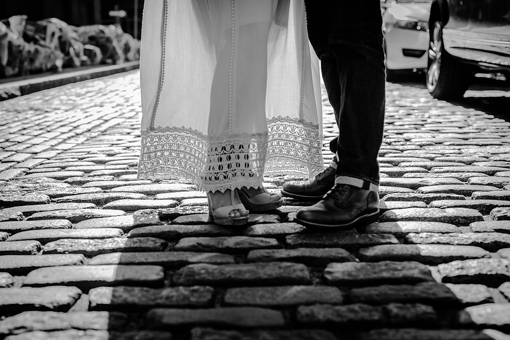black and white details photo of feet of expecting couple backlit with bright sunlight while standing on cobble stoned city street. photo by orange county family photographer krystil mcdowall