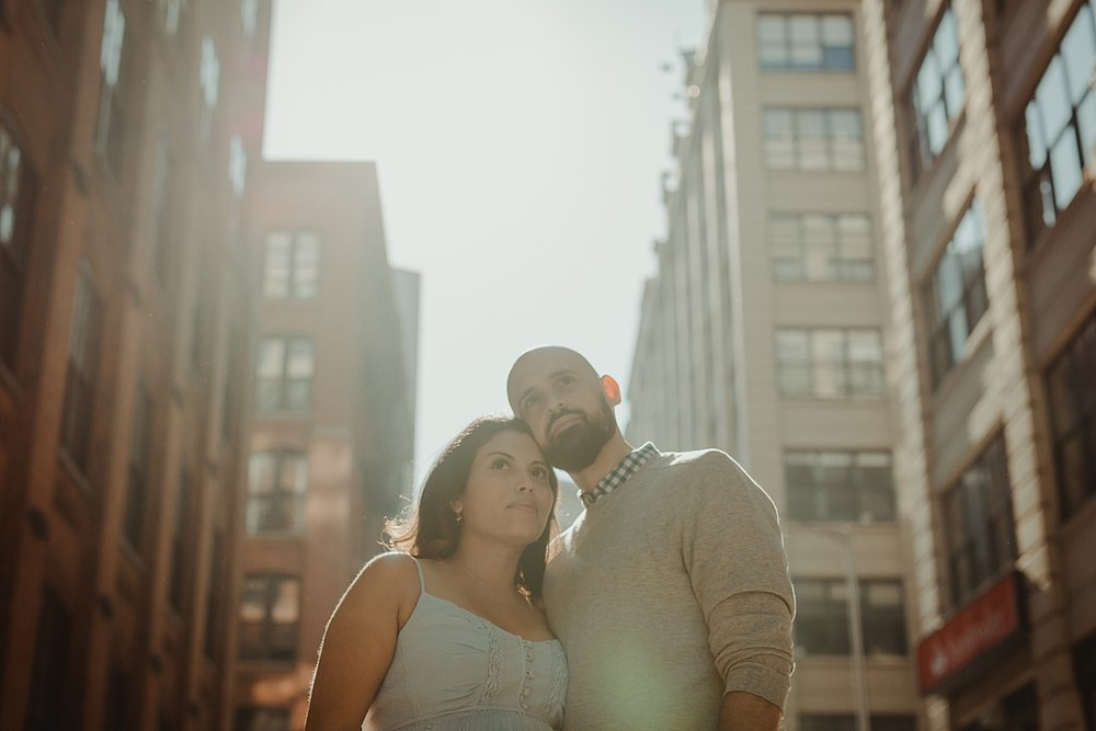 pregnant married couple stand in the middle of busy and bustling street with heads touching and looking out at the city streets for outdoor maternity photo session with orange county family photographer krystil mcdowall photography
