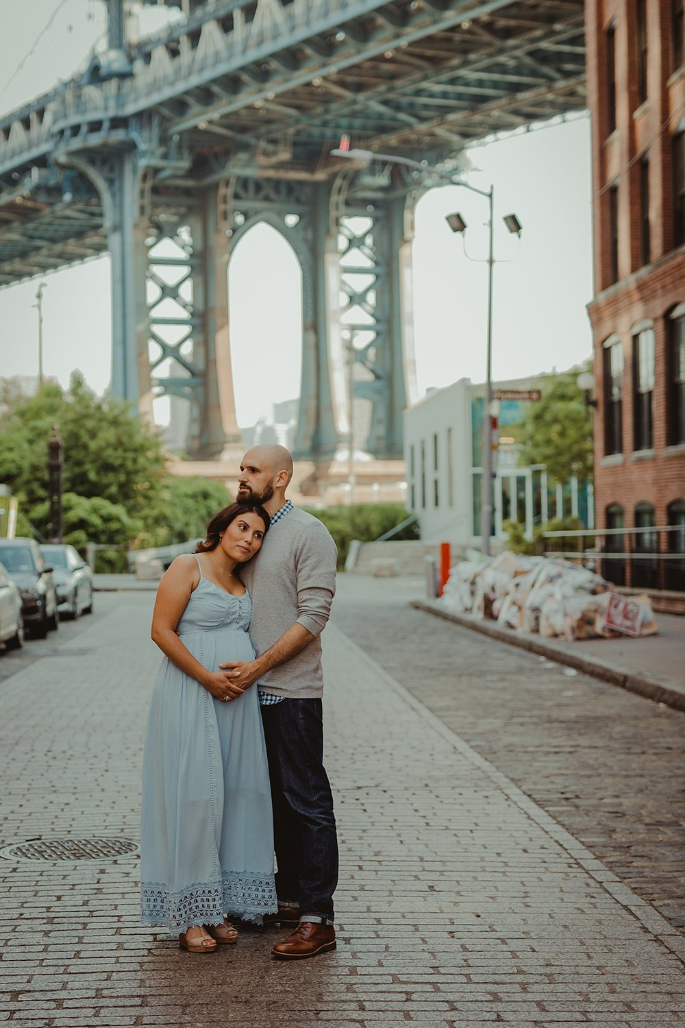 married couple stand in the middle of busy city street while husband holds wife's pregnant belly for outdoor maternity photo session with orange county family photographer krystil mcdowall photography