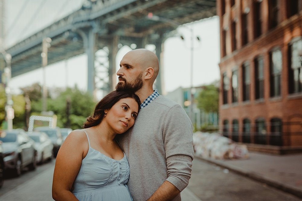 close up portrait of married couple standing in the middle of busy city street while husband holds wife's pregnant belly for outdoor maternity photo session with orange county family photographer krystil mcdowall photography