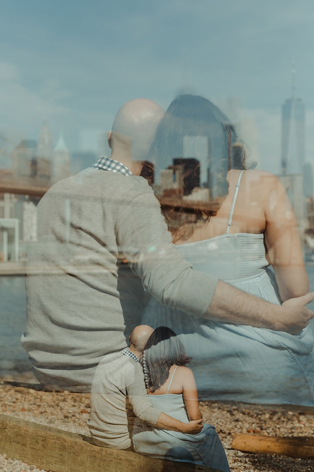 double exposure portrait of married couple sitting down and looking out at the busy cityscape during outdoor maternity photo session with orange county family photographer krystil mcdowall photography