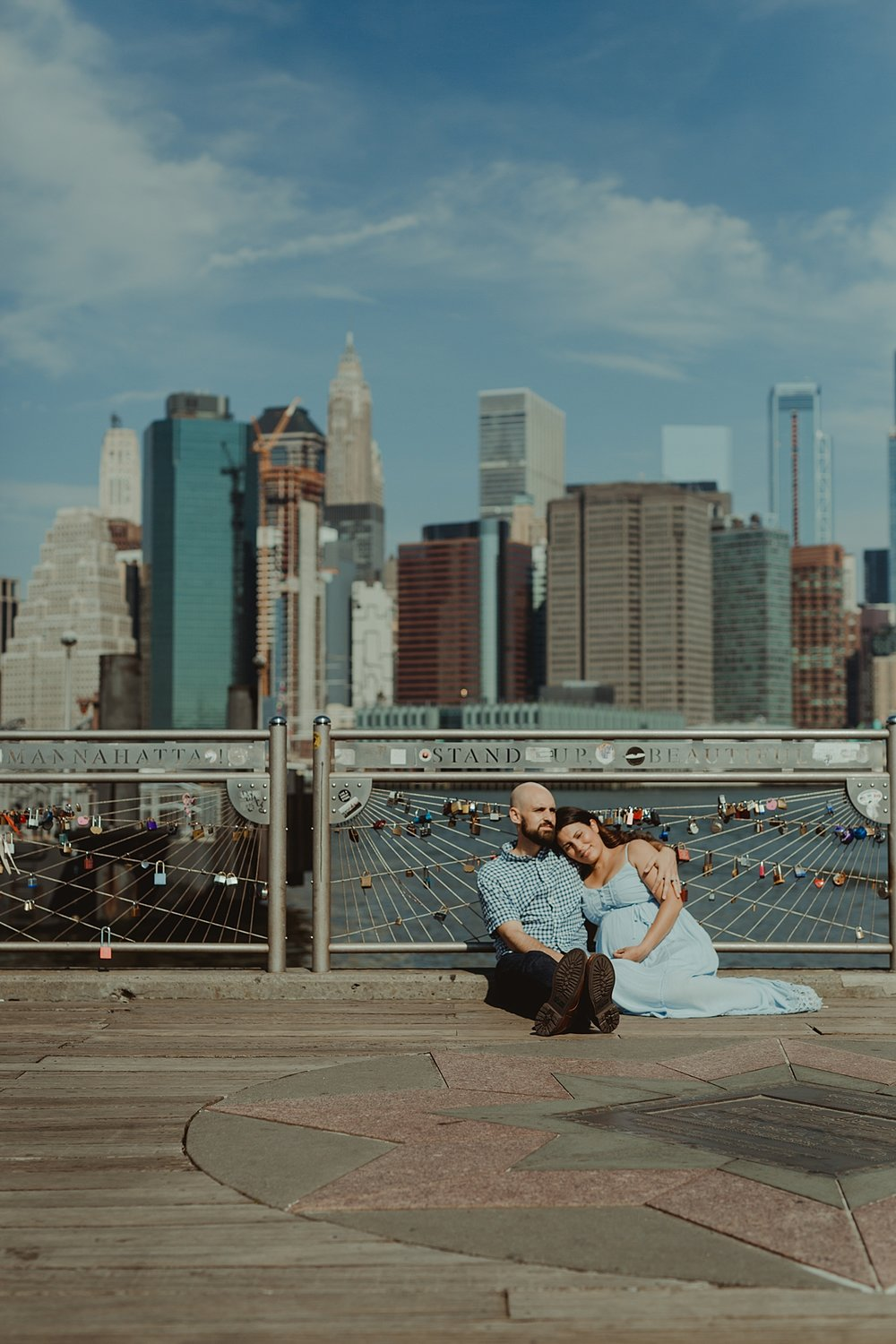 portrait of pregnant married couple sitting down together on river pier during lifestyle maternity photo session with orange county family photographer krystil mcdowall