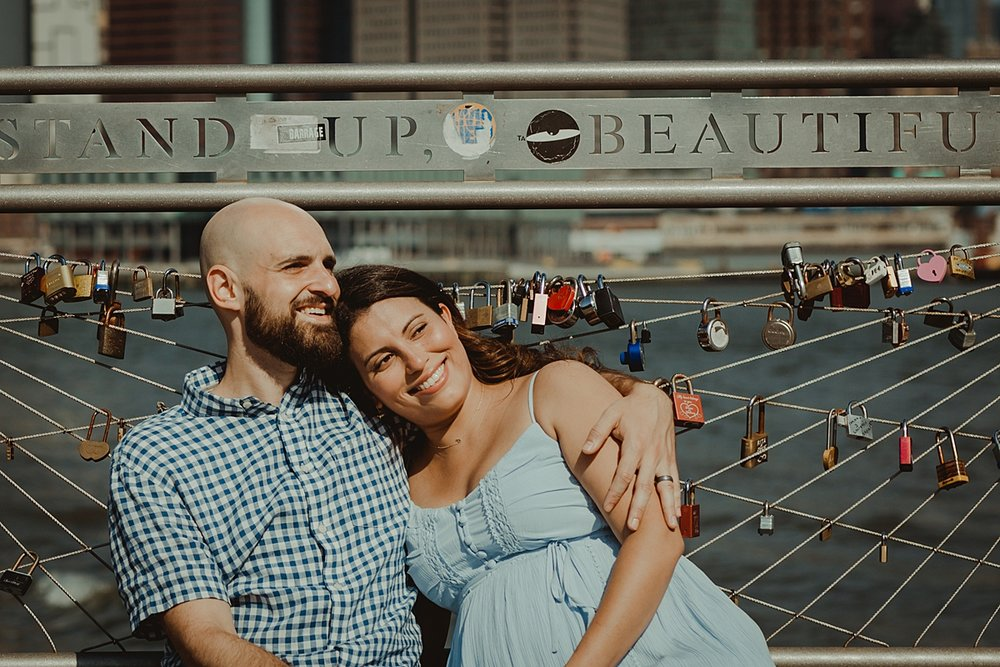 close up portrait of pregnant married couple laughing together and sitting down on river pier during lifestyle maternity photo session with orange county family photographer krystil mcdowall