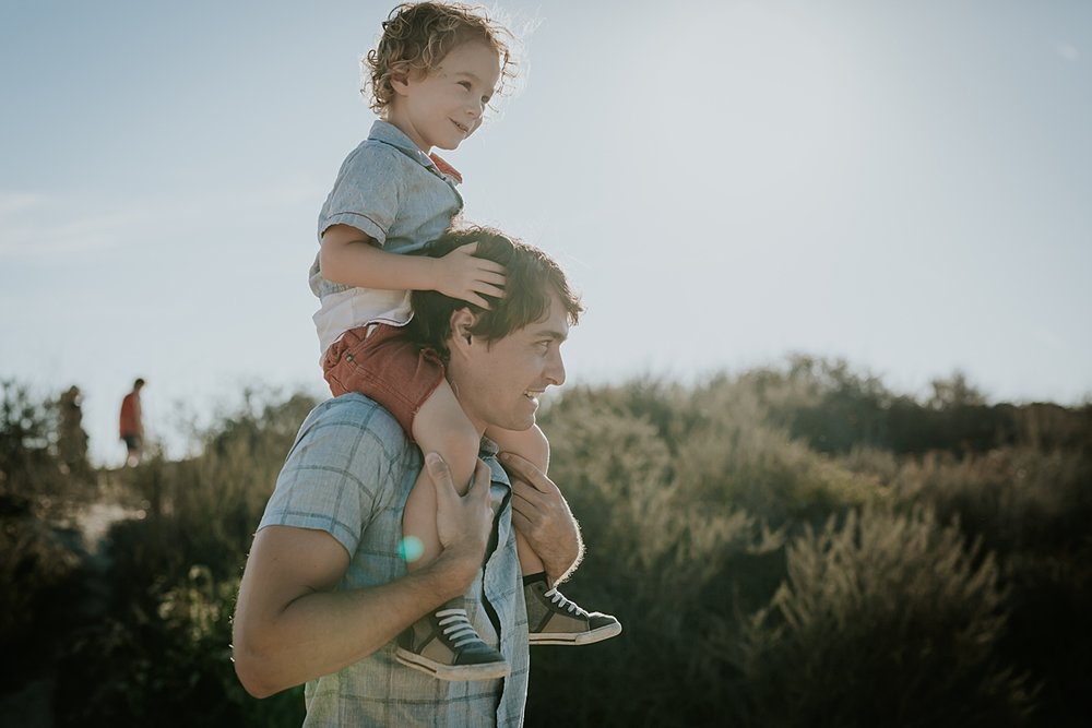 photo by Orange County family photographer Krystil McDowall. Candid photo of dad giving his toddler boy a shoulder ride at Top of the World Laguna Beach California