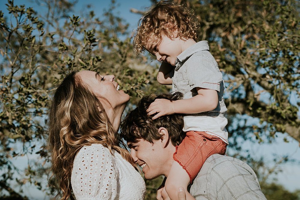 photo by Orange County family photographer Krystil McDowall. Candid photo of mom trying to kiss her sweet boy while dad gives his son a shoulder ride during outdoor family lifestyle photo session at Top of the World Laguna Beach California