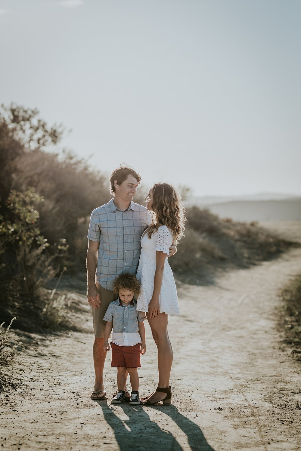 photo by Orange County family photographer Krystil McDowall. Photo of dad, mom and son standing on dirt road during outdoor family lifestyle photo session at Top of the World Laguna Beach California