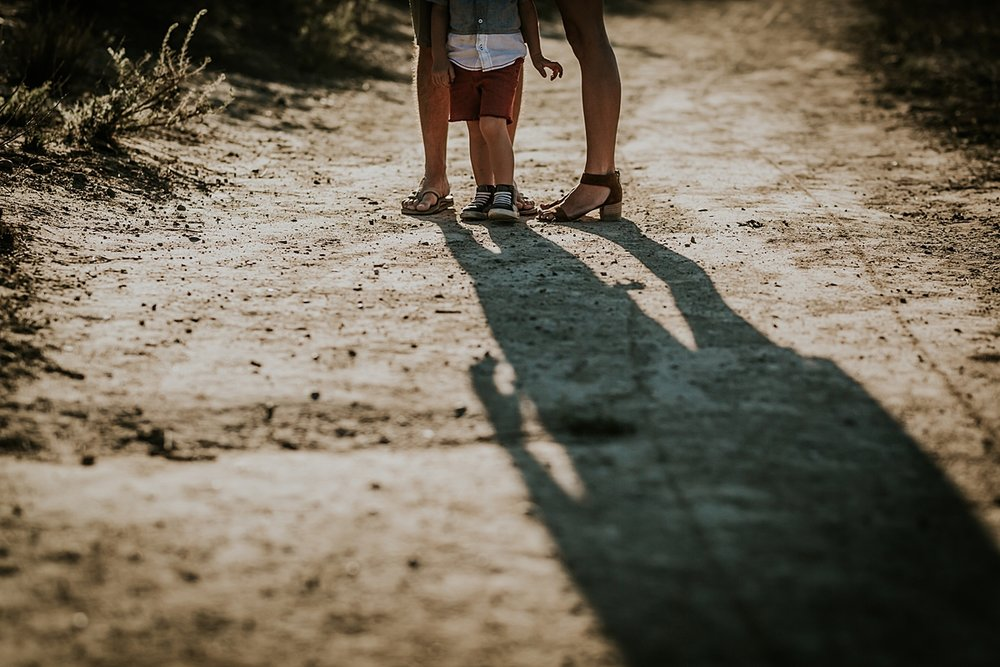 photo by Orange County family photographer Krystil McDowall. Details photo of family feet standing on the dirt road with long shadows falling in front during outdoor family lifestyle photo session at Top of the World Laguna Beach California